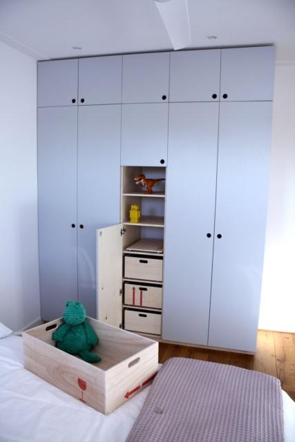grijze kledingkast voor de kinderkamer, met een van de speelgoedbakken uit de kast.
